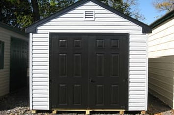 White storage shed with black doors